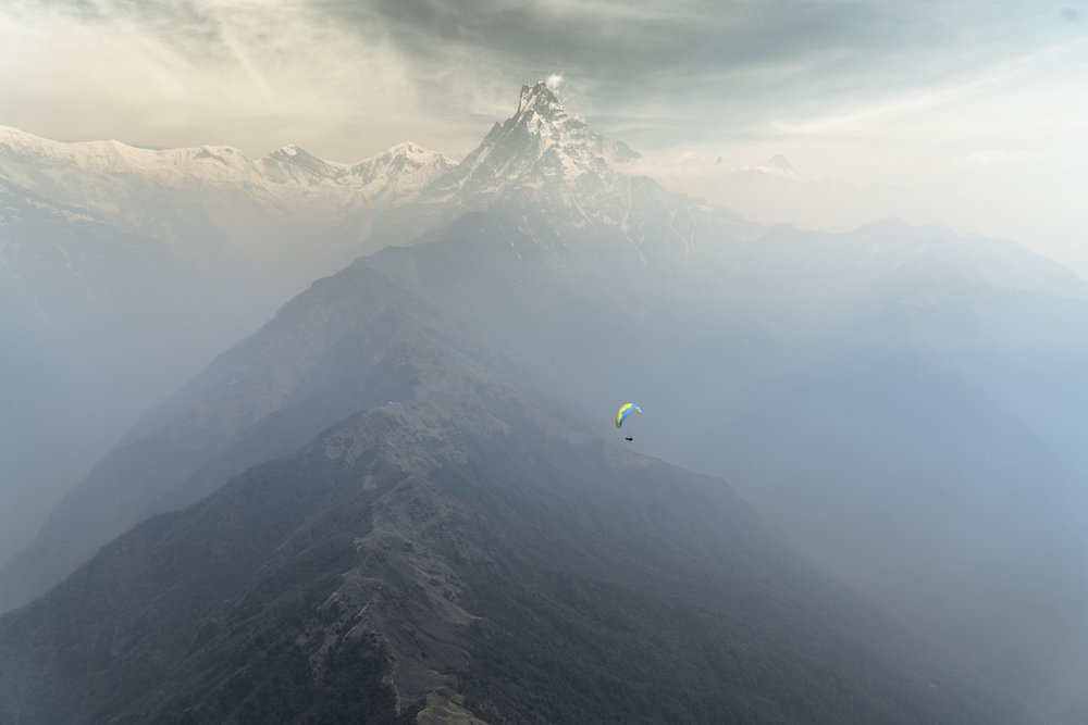 Soaring high above the foothills of the Annapurna Range Cody Tuttle sets off on his first and probably most memorable XC flight of his life. Taking off above 3,700 meters on the Mardi Himal ridgeMachapuchare (6,993meters) still stands tall in the distance.  Photo:  Cherise Tuttle  flying tandem with  Jamie Messenger