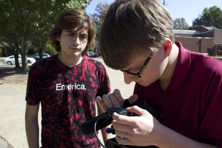 Supervising videographer Matt Sloan works with videographer Daniel Jaramillo to fix an audio issue.