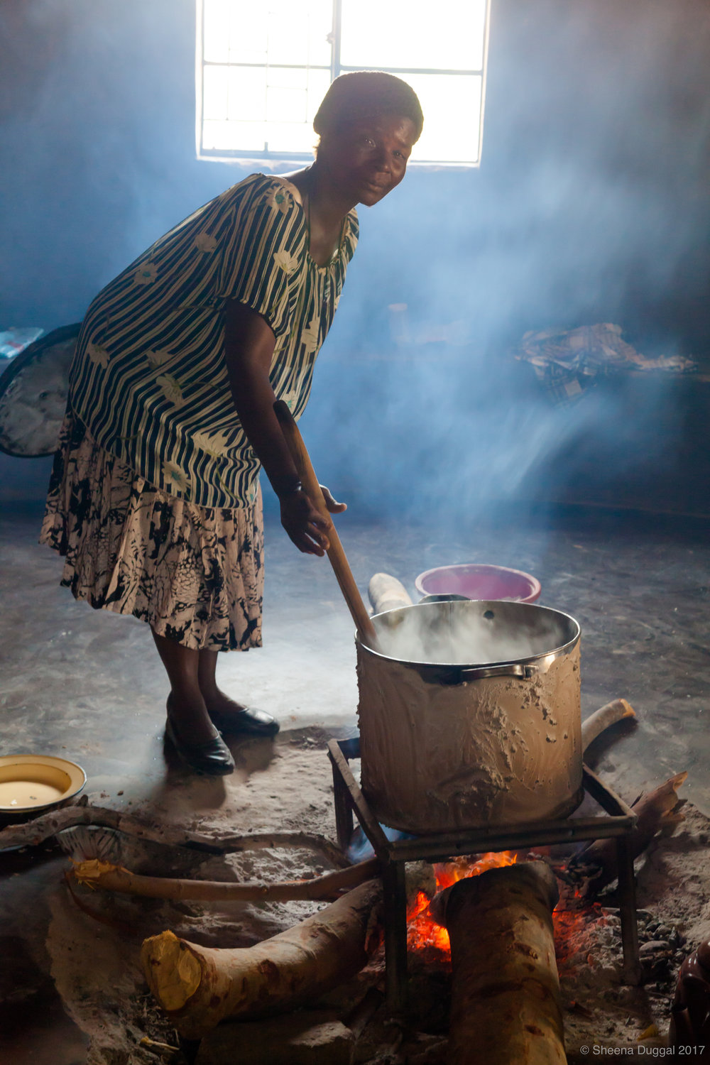 Cooking for orphans in a roundavel. (round  thatched  mud huts). Cough!
