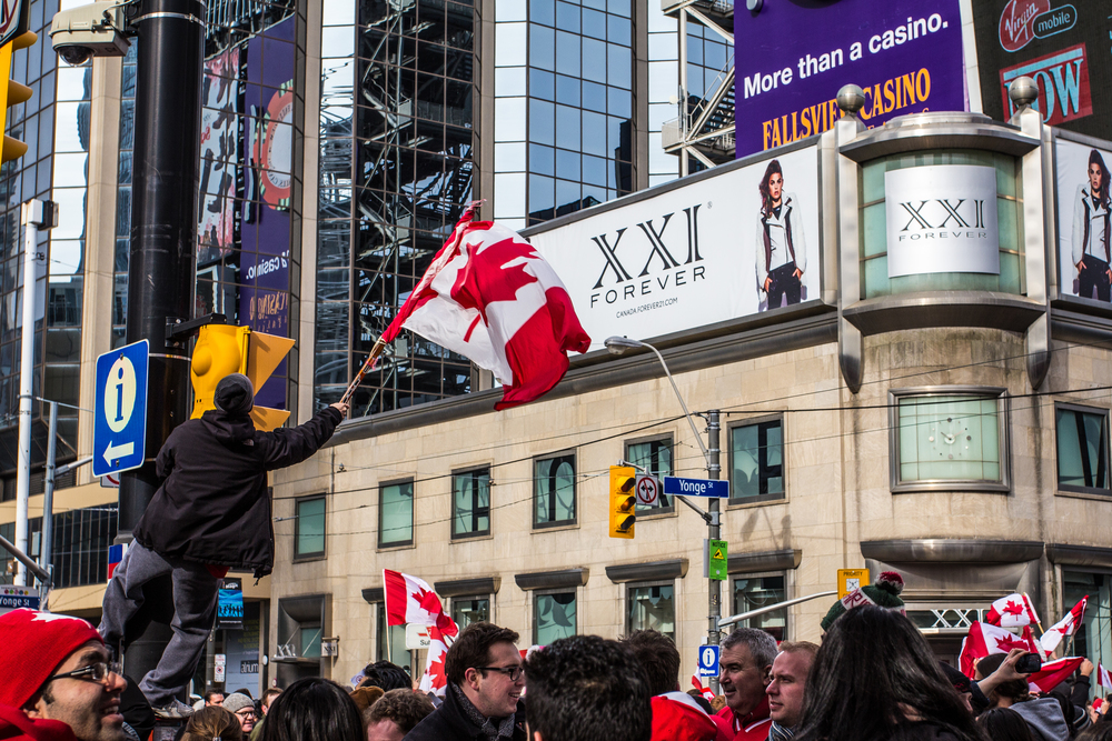 A man waves a Canadian flag from a lamp post as celebrations pour into the streets of Toronto following Canada's 3-0 gold medal victory over Sweden in Men's Ice Hockey at the 2014 Sochi Olympics.