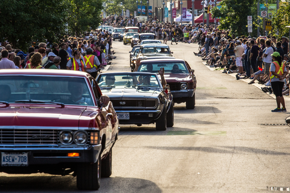 Cruisers wave to the crowd during the 24th annual Cruising on King classic car parade in Downtown Kitchener.