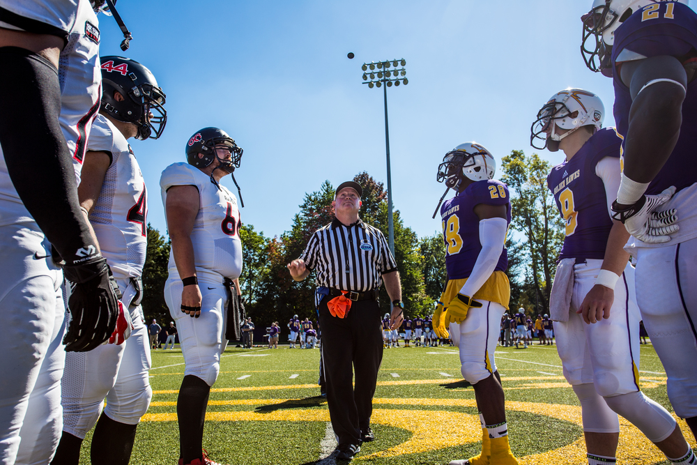 Captains from both Laurier and Carleton football teams watch as the head referee flips the coin to determine sides at Laurier's Homecoming Game.