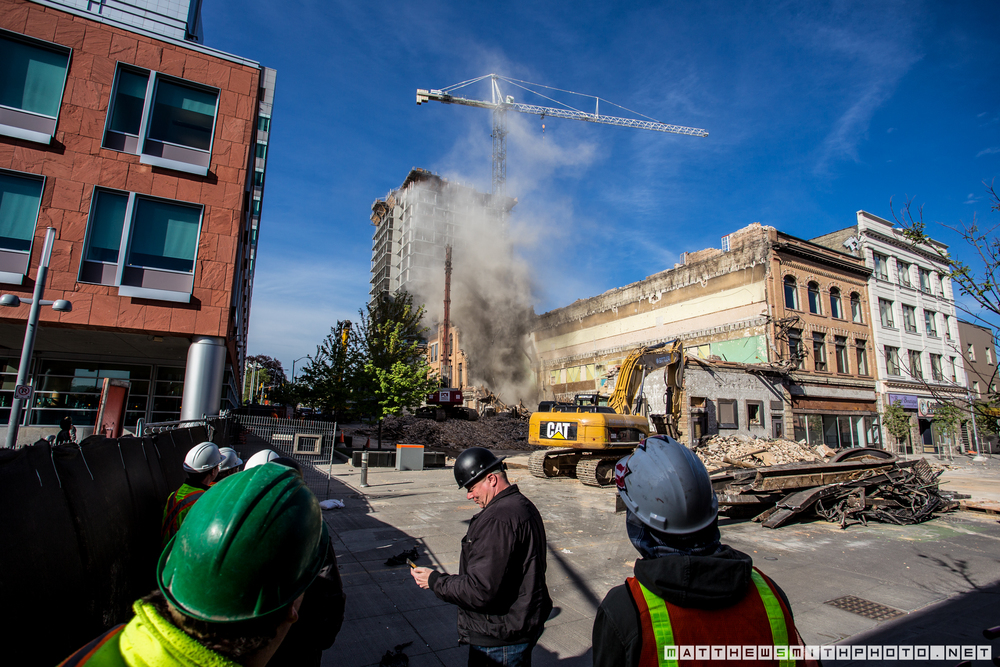 Demolition workers watch as the historic Mayfair Hotel is dismantled after a water main break caused irreparable damage to the buildings foundation and structure.