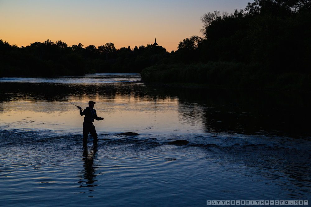A fisherman casts into a shallow section of the Grand River as dusk falls near the Pioneer Tower.