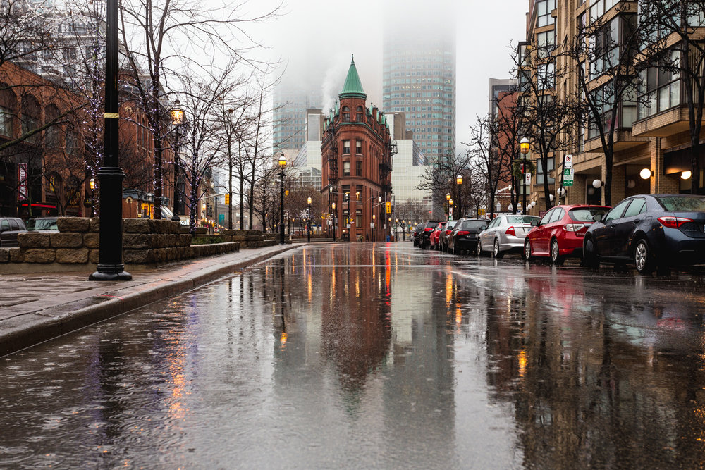 The infamous Flatiron building reflects on the soaked streets during a January rain shower in Toronto.
