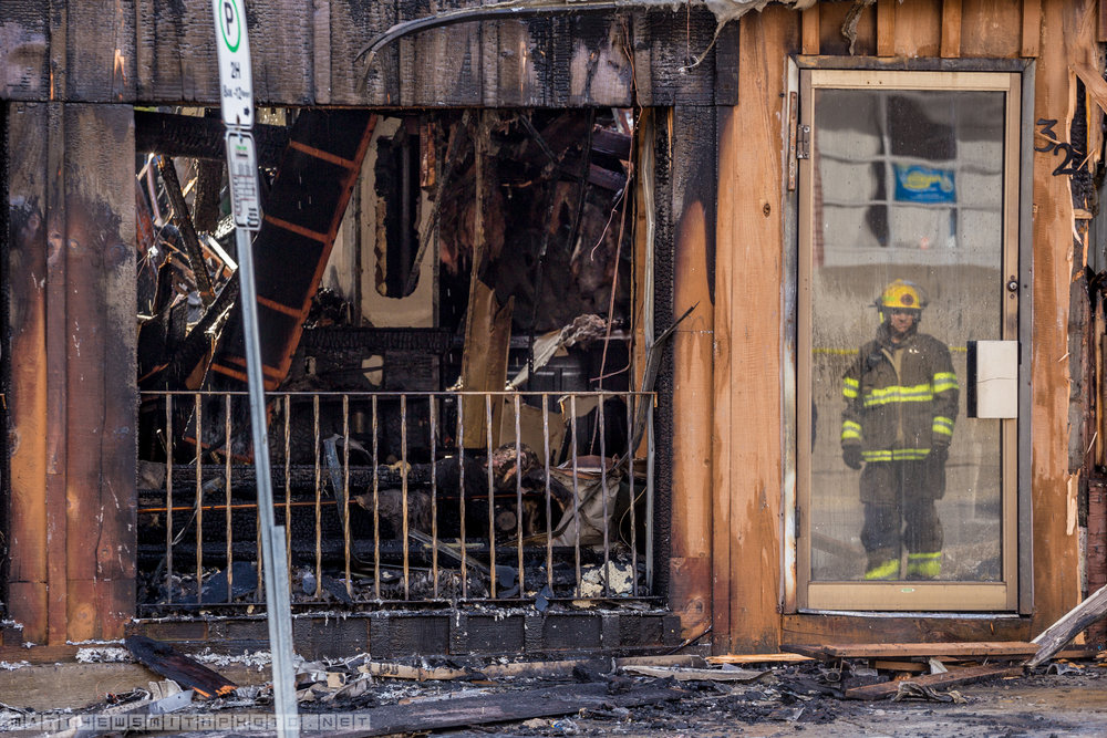 A firefighter is refelcted in the front door of Marina's bar in Downtown Kitchener as he surveys the damage from an early morning fire that tore through the two-storey bulding.