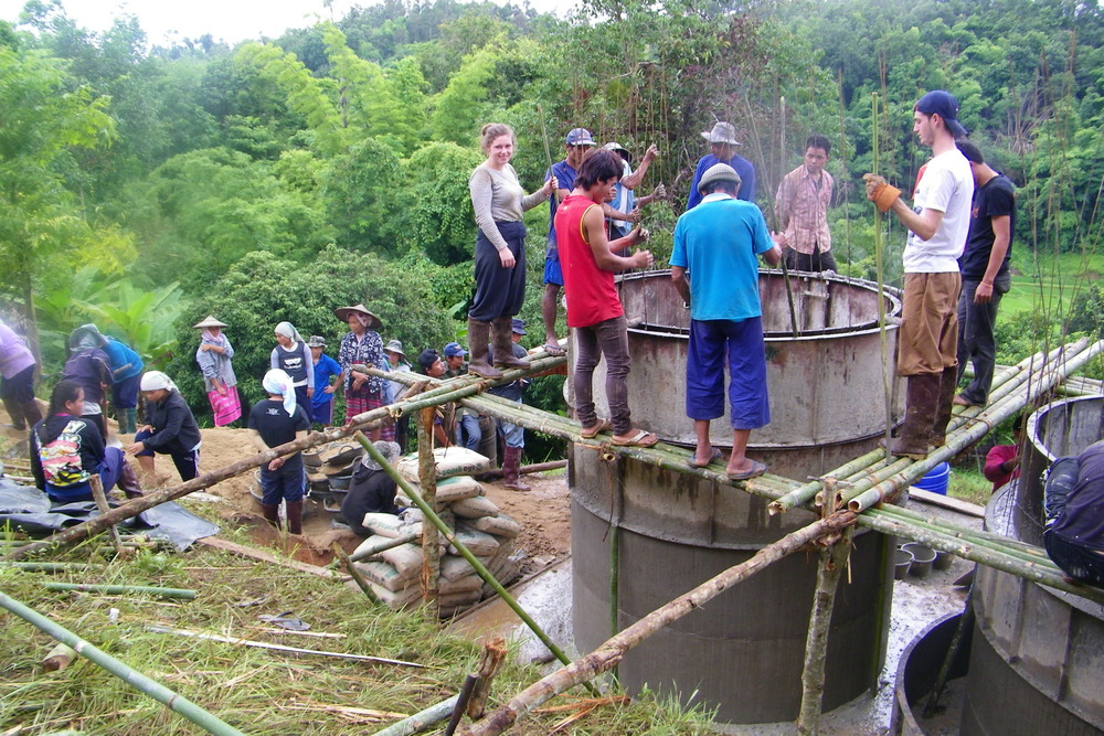 Volunteers and Karen Hilltribesmen work together to build the filtration tanks