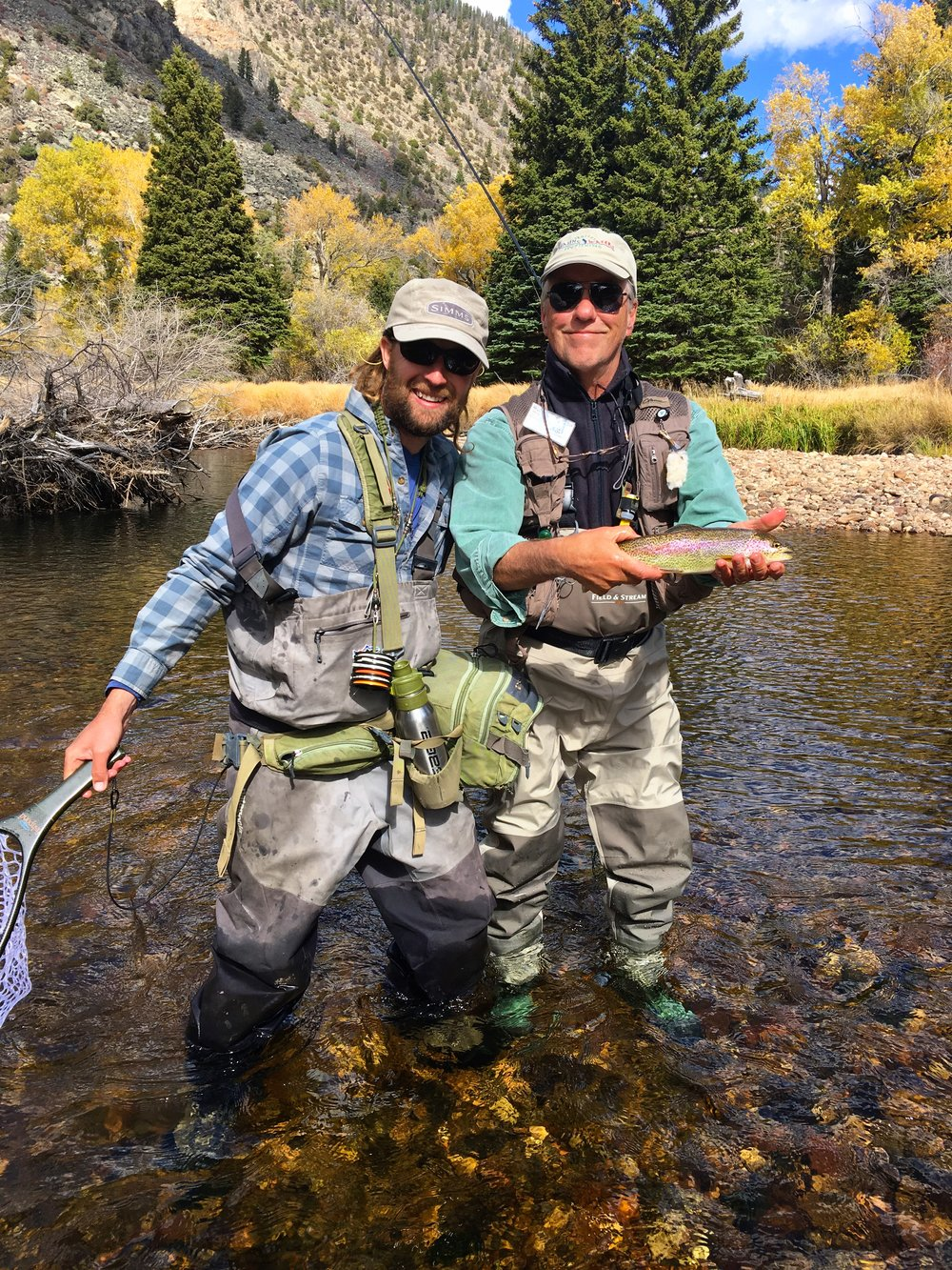 Tom and Chris display a pretty rainbow trout, before returning it to the water