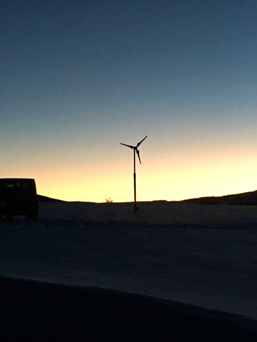 Sun sets behind the wind turbine