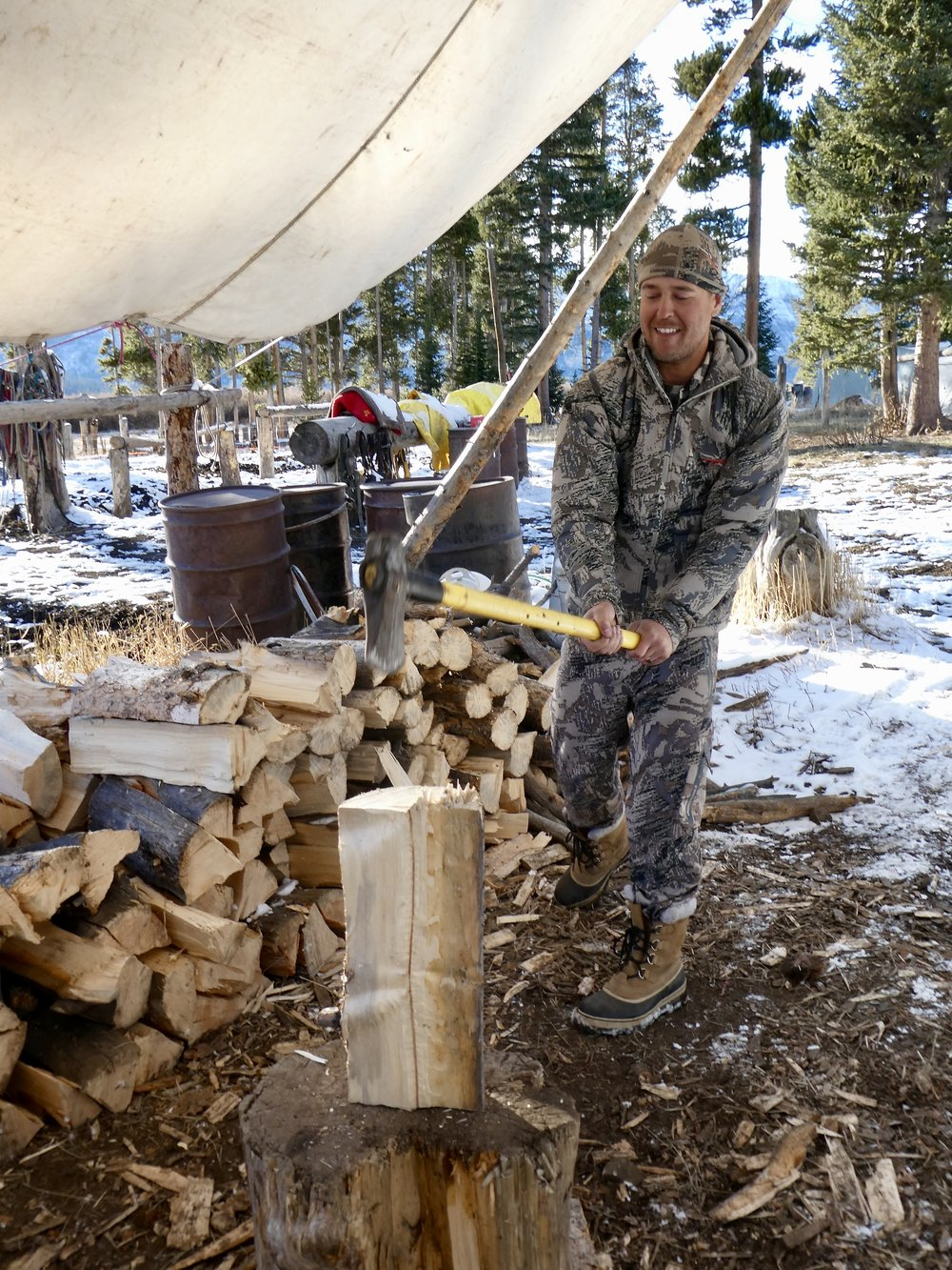 Ben keeps warm and passes the time by splitting wood