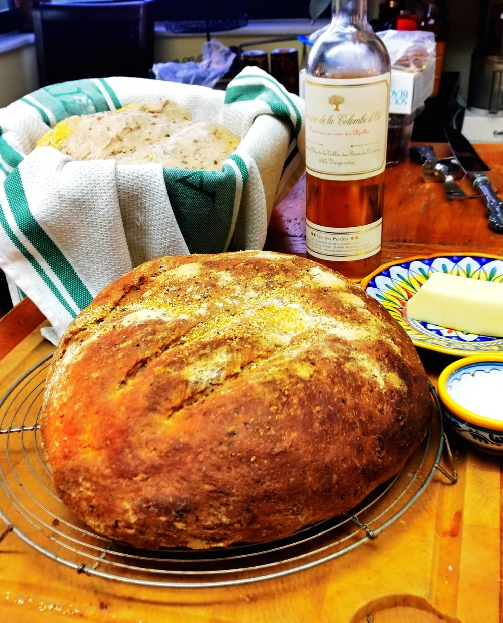 My spent grain loaf, baked in the foreground an a risen loaf about to be put on the baking stone in the background, with the best accompaniments: salt, butter and olive oil