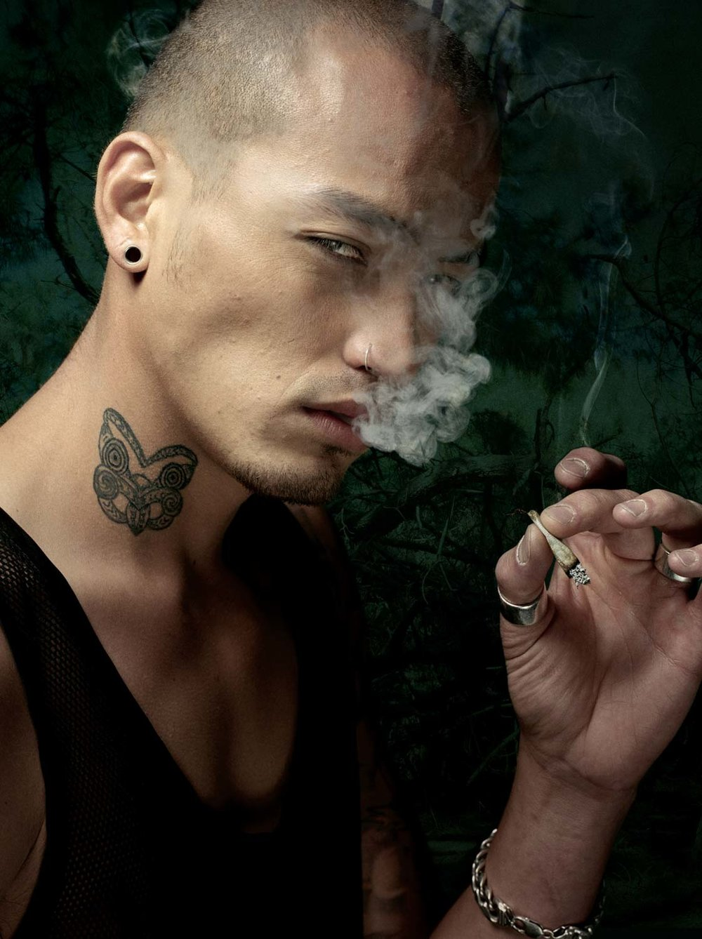 Serious Man Smoking With Tattoo On His Neck