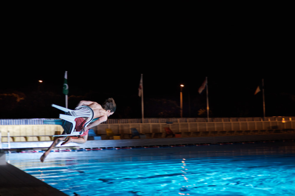 Guy Jumping Into A Pool On A Chair