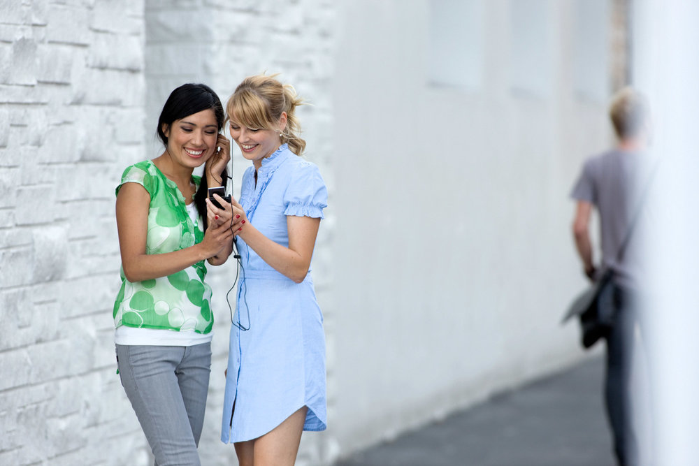 Two Girls Looking At Phone And Sharing Headphones