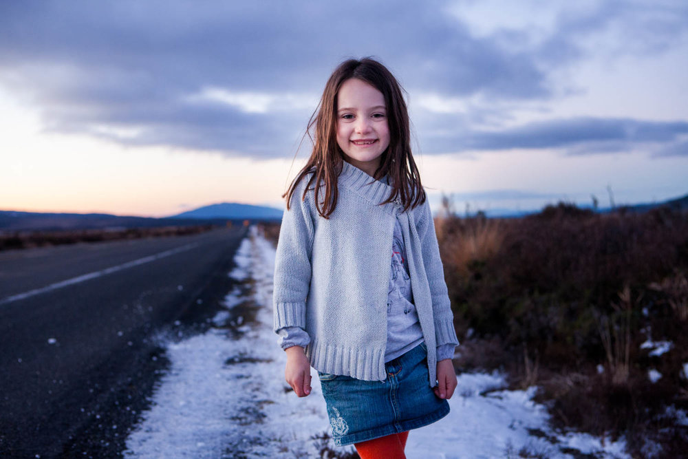 Young Girl Standing On The Road Next To The Snow