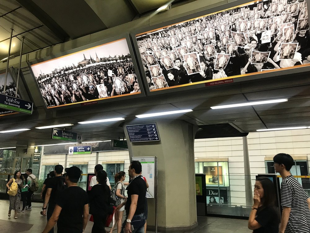 BTS Skytrain Saphan Taksin. Video footage of the King displayed throughout the station...