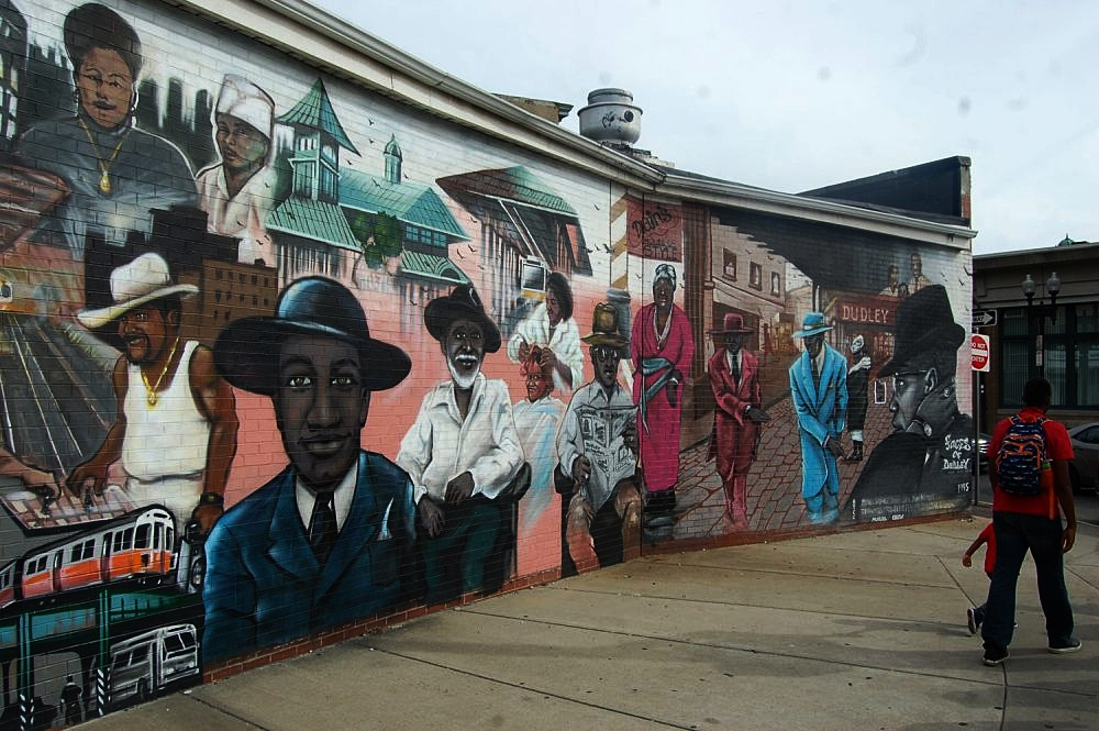 """Faces of Dudley"" mural by Mike Womble and Mayor's Mural Crew, Completed in 1995. Photo Credit: Greg Cook for WBUR"