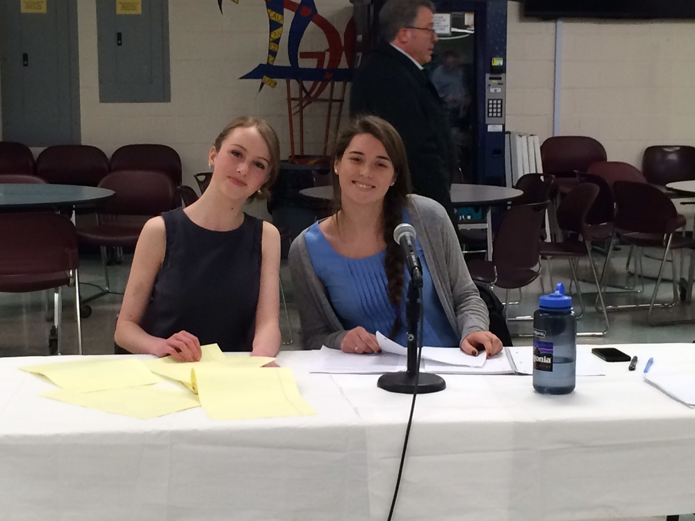 Meg and Em at Table in Exhibition Debate