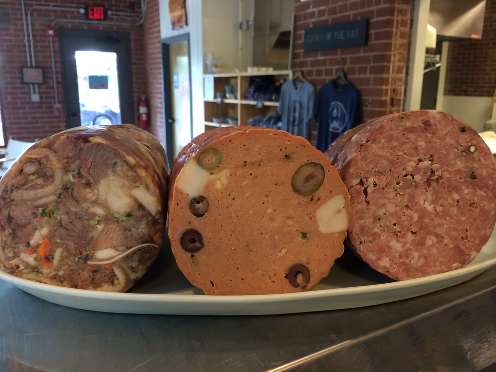 From left to right, we have head cheese - a delicious European delicacy that is essentially a terrine made from the tasty parts like cheeks and tongues, Mortadella, and Salami. All made in house, of course!