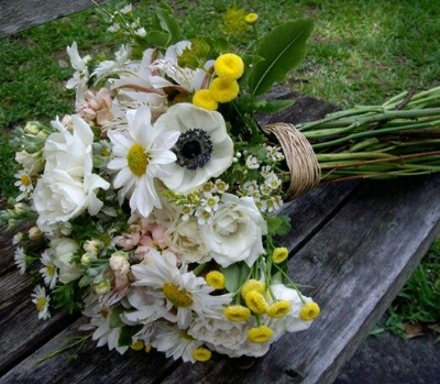 Wildflower bouquet with daisies, white anemone flower (the one with a black eye),small yellow pompom mums, white lisianthus, small white waxflowers, light pink stock flowers, and white alstromeria.