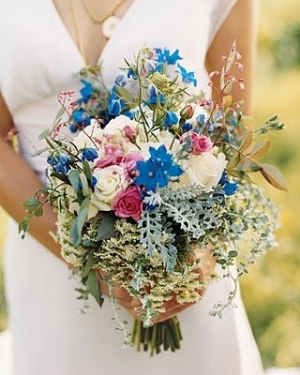 A dreamy wildflower bouquet of blue delphinium, roses, eucalyptus, Queen Anne's Lace, dusty miller, and assorted leaves.