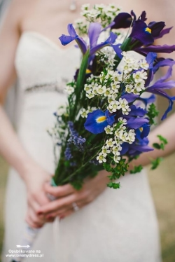 A garden iris and waxflower bouquet with bupleurum vines and assorted leaves.