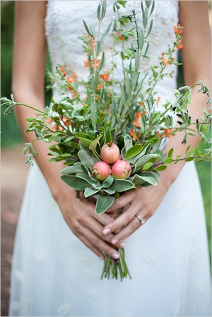 Rosemary and sage are a great base for the orange and deep purple kangaroo paw flowers in this bouquet. We also love the idea of little apples or pomegranates in the center of this bouquet.
