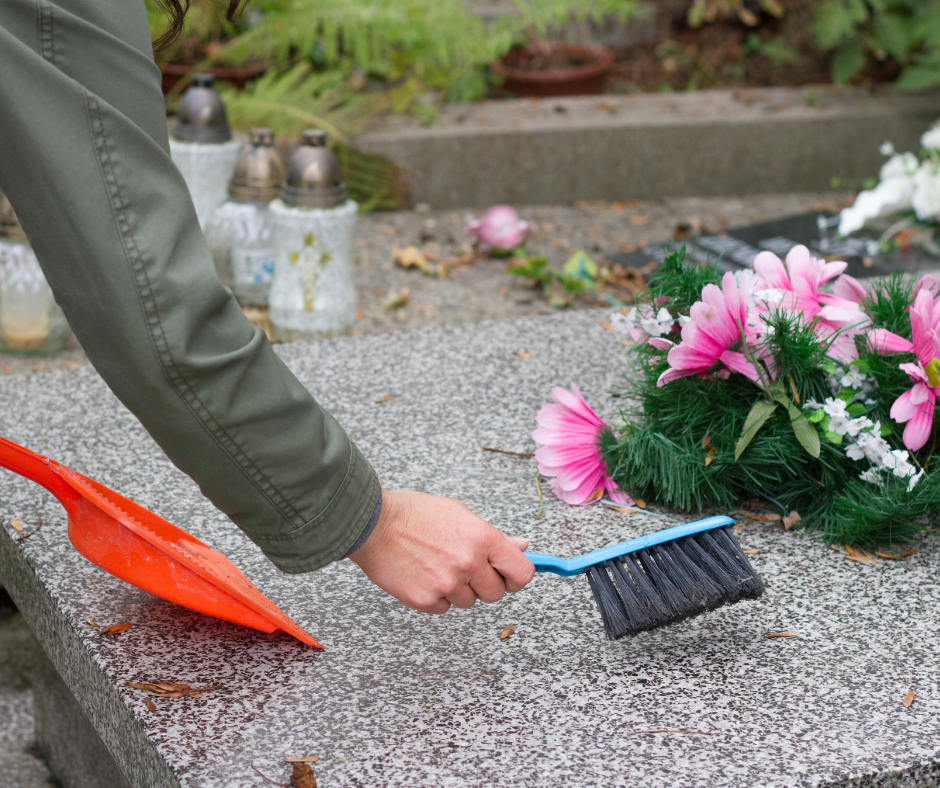 Sweeping the gravesite at a cemetery in time for All Saints' and All Souls' Days.