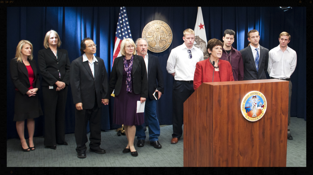 Podium: San Diego District Attorney Bonnie Dumanis photographed with victims Keith Robertson, Brandon Scheerer, Evan Henderson, & Jason Fiori. Left: Fred & Kathy Santos.