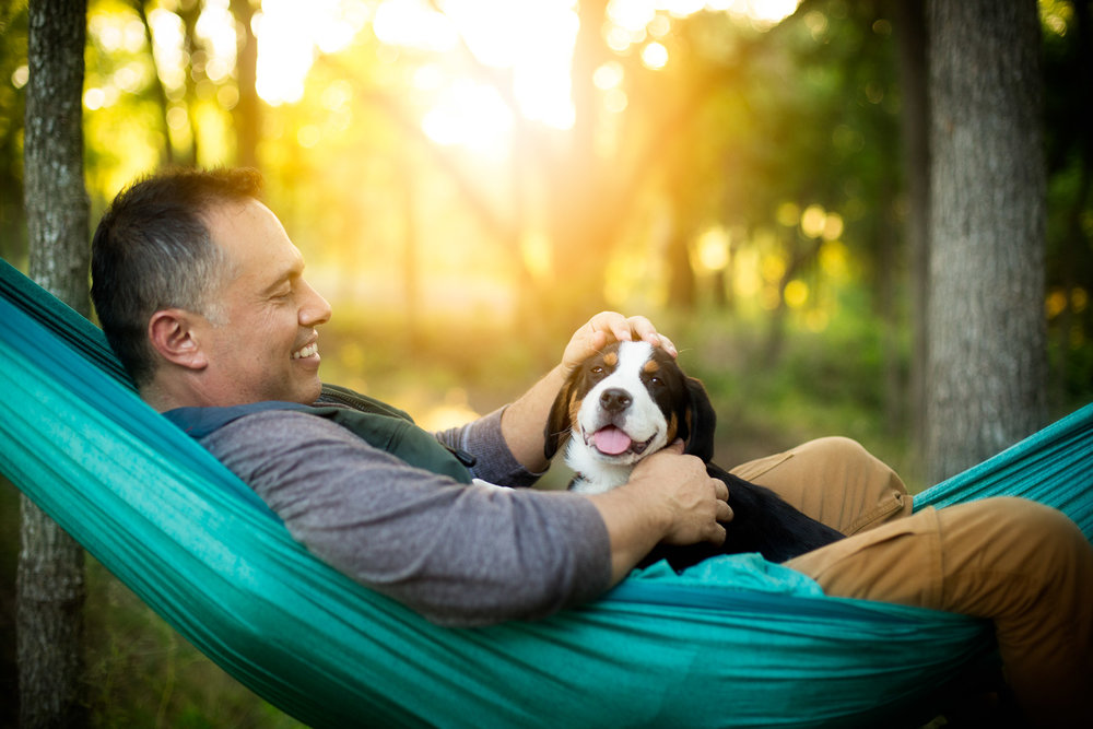man-with-dog-puppy-on-hammock-camping-dog-photography.jpg
