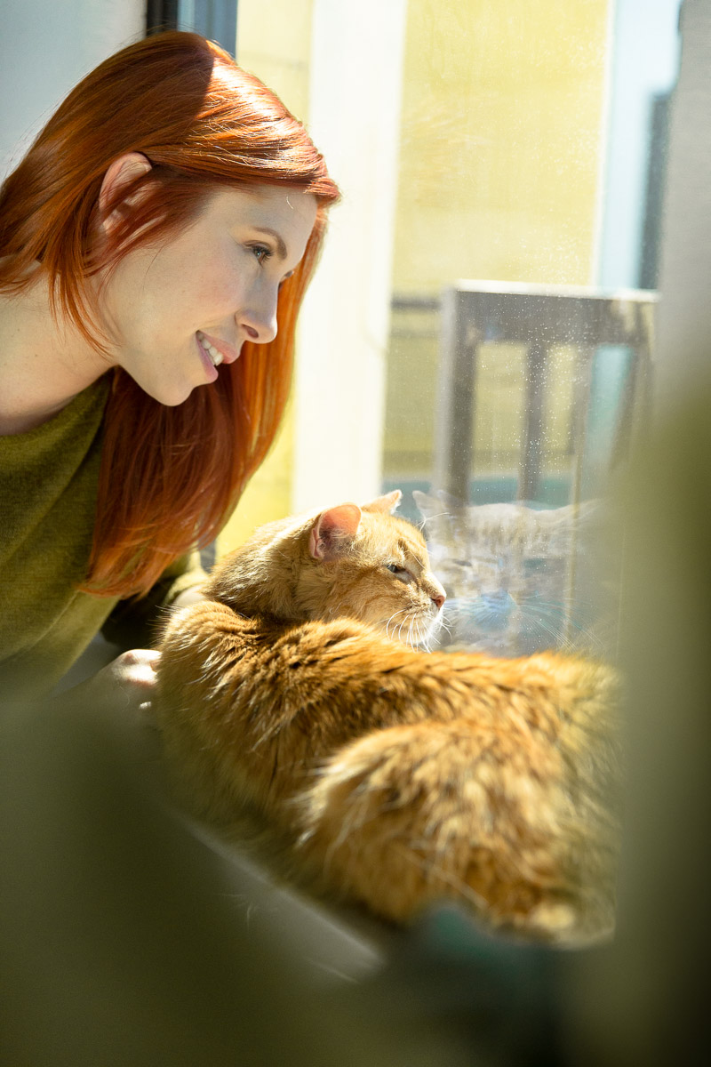woman-with-cat-looking-out-window-apartment-cat-photographer.jpg