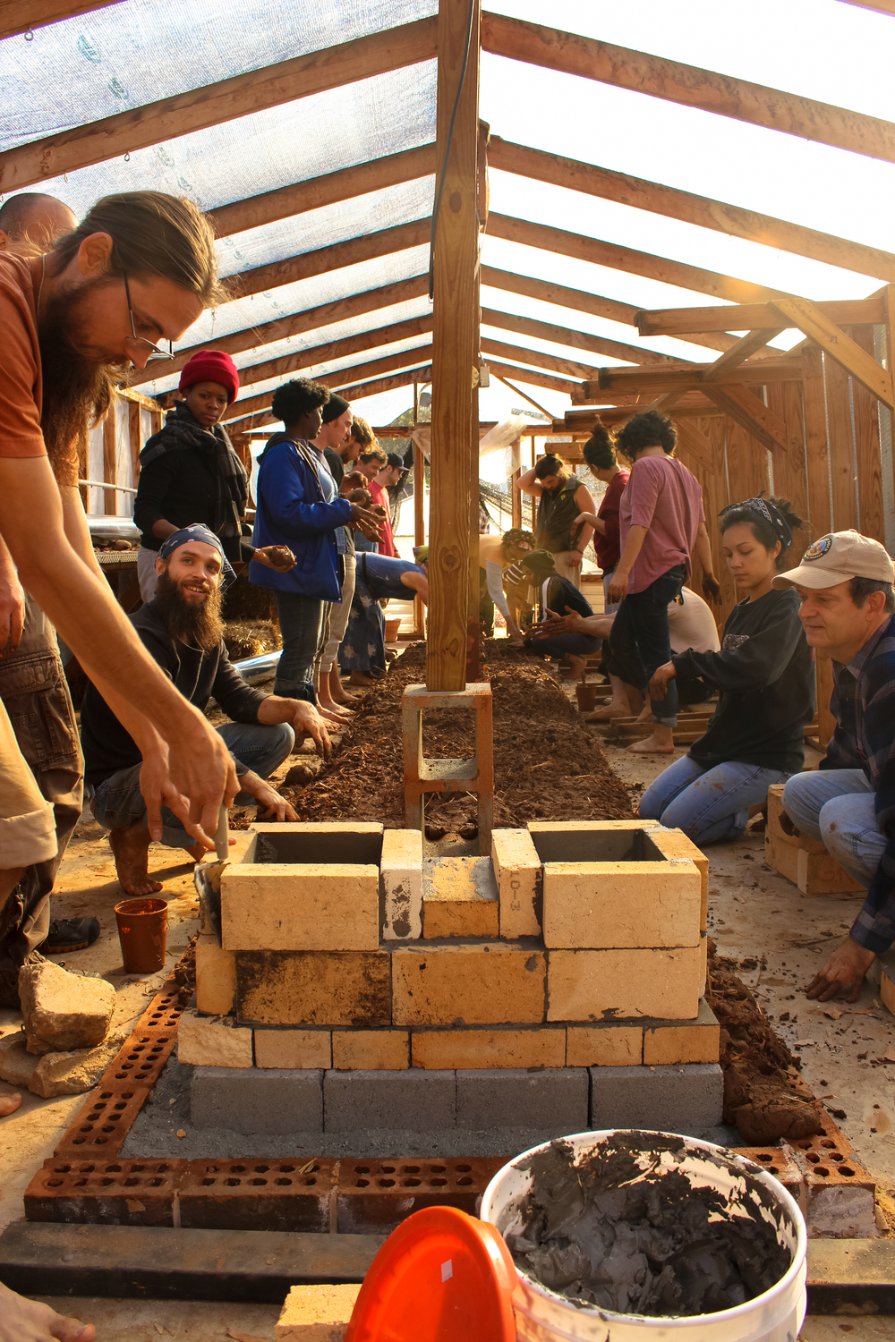 Aviva with the Mud Builders of Atlanta and Corwin May with Georgia Tech's Arkfab lead volunteers at Wheat Street Garden as they build the cob thermal mass part of the rocket stove.