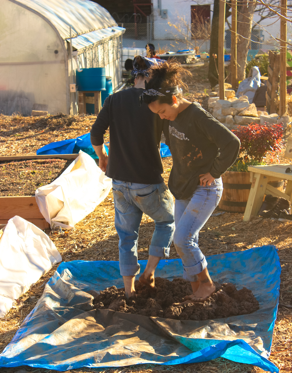 "Karina and Steve do the ""cob dance"" at Truly Living Well's Wheat Street Garden as they mix clay, sand and straw for the earthen concrete ""cob"" (a sustainable, chemical-free building material)."