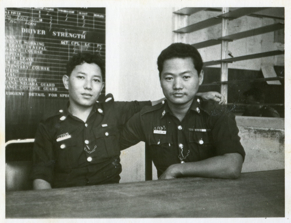 Arun Kumar Tamang (left) seated in the Motor Transport (MT) section office. The Singapore Gurkha seated beside him is his senior. Date: Unknown. Photo Collection: Aswin Tamang / SGPM.