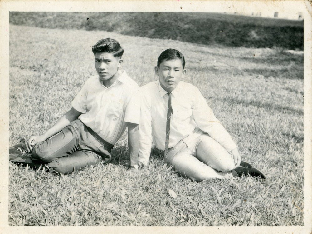 Shivraj Thapa (left) and Sahadeo Thapa sitting on the grass at Mount Vernon Camp, during the Dasain holidays. There was a Chinese man who visited the camp to take photographs of everyone. He returned to sell Shivraj a copy of this photograph. Date: 1970. Photo Collection: Shivraj Thapa / SGPM.