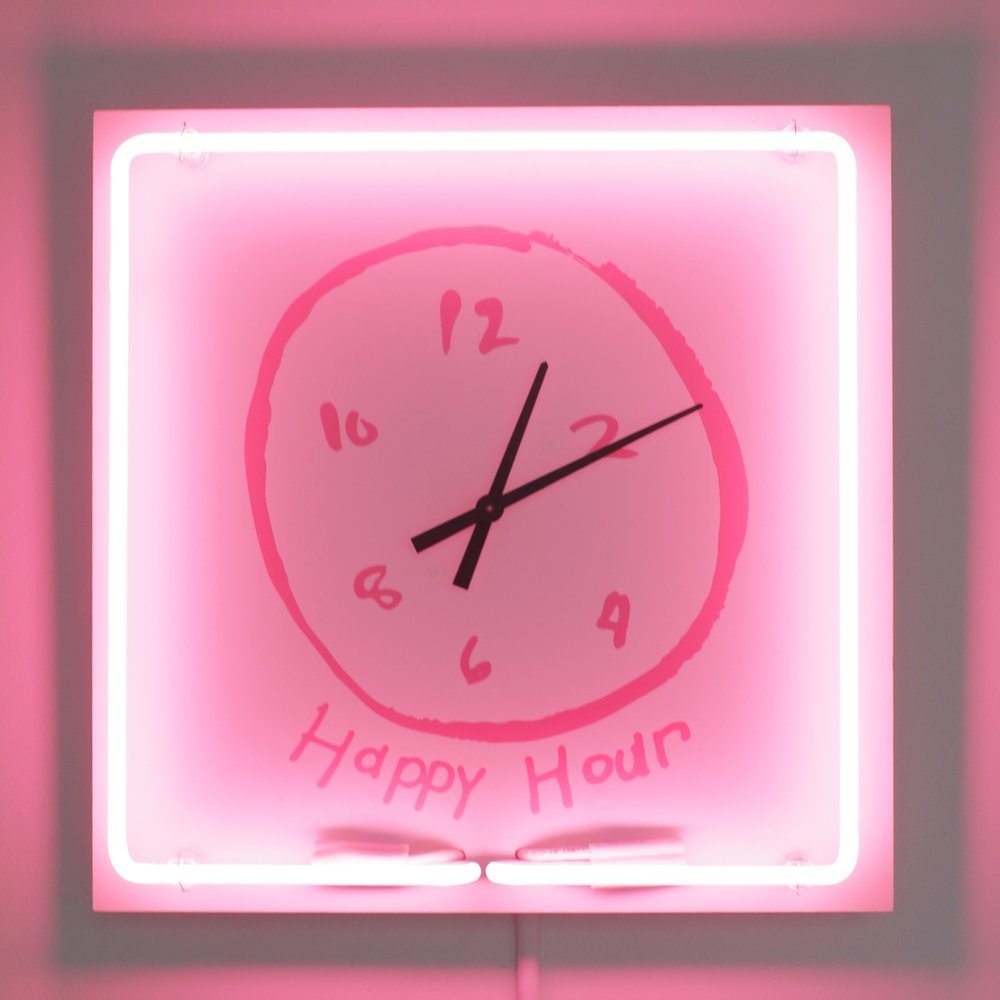Happy Hour Clock,  2018  Clock face and neon mounted to white powder-coated board  18 x 18 x 3 inches  The centerpiece of the  Rosé Room , Hovnanian's  Happy Hour Clock  runs in hyperspeed. The clock hits 5:00 pm at least once an hour - happy hour is never that far away. The neon border pays a nod to bar signs, casting a pink glow on the wall of drawings that feature icons and aftermaths of American drinking culture.