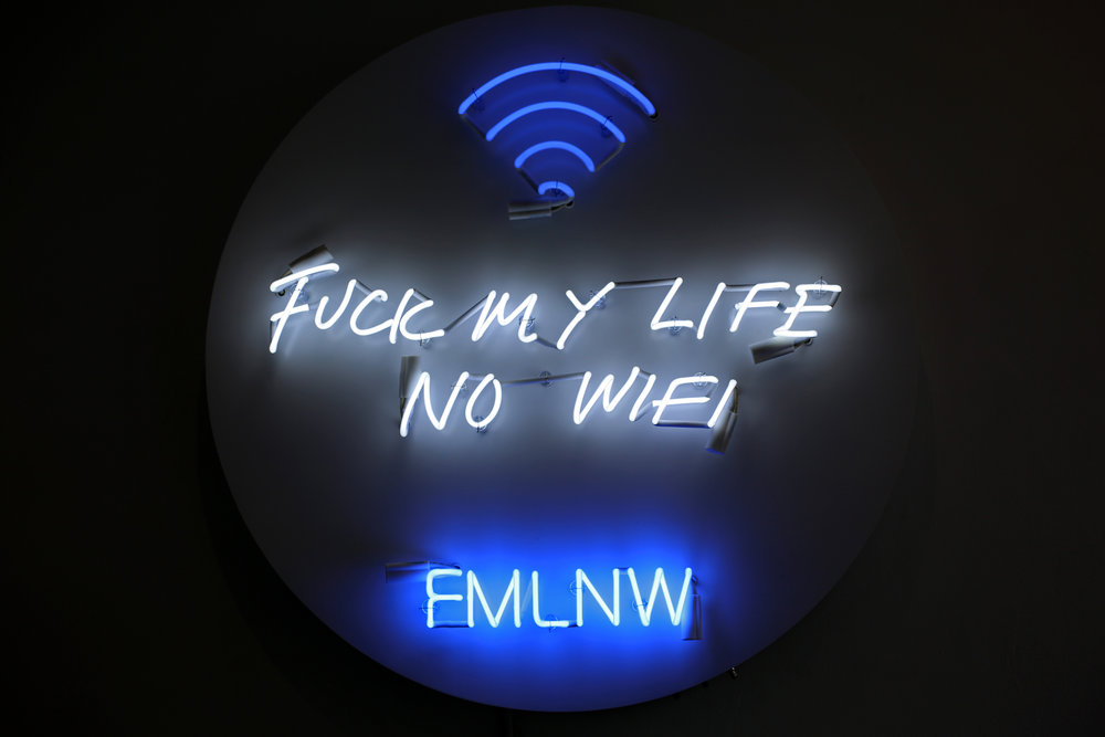 FMLNW , 2018  Neon mounted to white powder-coated aluminum  36 inches diameter  Hovanian's  Acronym Neon  series features works in neon that express emotionally raw phrases in acronyms, our new digital language. In the age of the internet and ubiquitous smartphone use, our modes of expression have been shortened. Communication occurs quickly and abruptly, without as much emotion. In this series, Hovnanian explores how the meaning behind our language has become sterilized by digital technology.