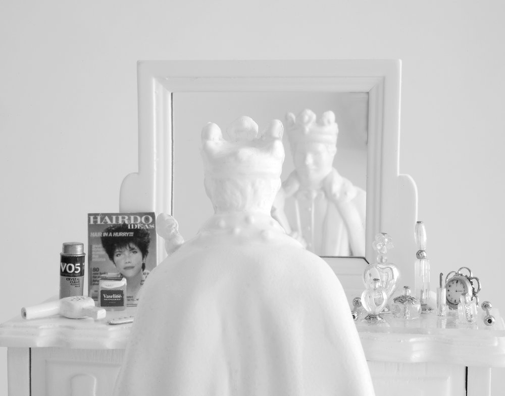 Close Shave , 2010  Photograph in archival ink on rag paper  32 x 26 inches   Close Shave  presents an anonymous white figurine of a man viewed from behind, crowned and robed as he looks at his reflection in a vanity mirror. In front of him, the surface of the vanity is laid out with recognizable beauty products. The piece suggests the idea that beauty culture extends beyond gender boundaries, inflicting another set of related ideals onto men as well as women. No one is immune to its pressures.