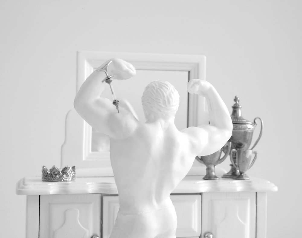 Natural Athlete , 2010  Photograph in archival ink on rag paper  32 x 26 inches   Natural Athlete  is another work in Hovnanian's  Too Good to Be True  series that reminds the viewer that the pressures of societal ideals cross gendered lines. In  Natural Athlete,  a male athlete in a speedo is shown from behind, flexing his arms in front of a vanity mirror. On the table, an array of trophies is laid out. A needle protrudes from his bicep, alluding to the use of steroids to build muscle mass. In this portrayal, the man appears smitten with his own figure, harking to the overarching theme of the series: visualizing societally-propelled narcissism.