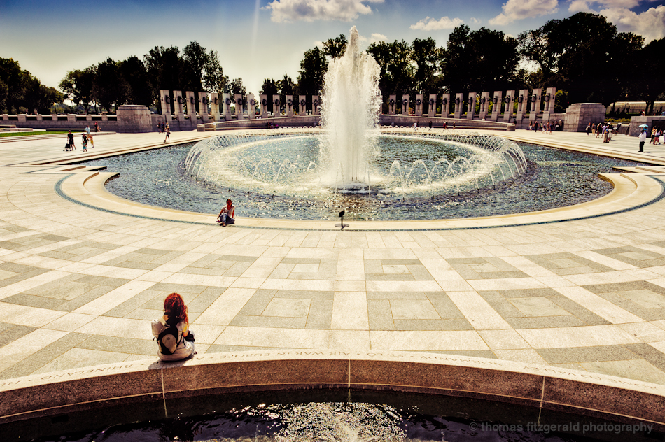 A Girl sits observing the fountain in the World War II Memorial, Washington DC.