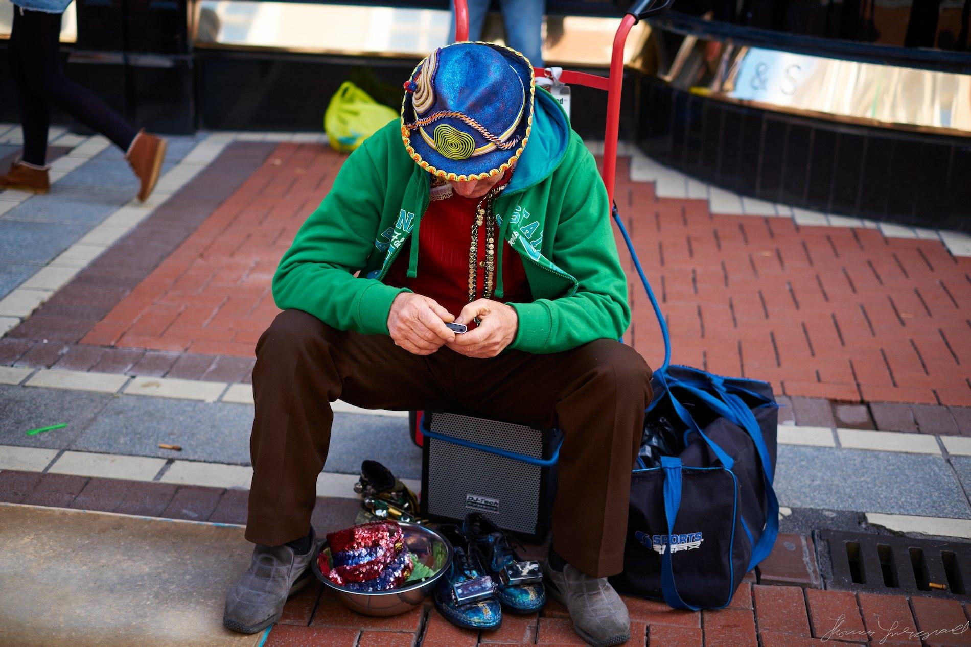 Street busker on smartphone