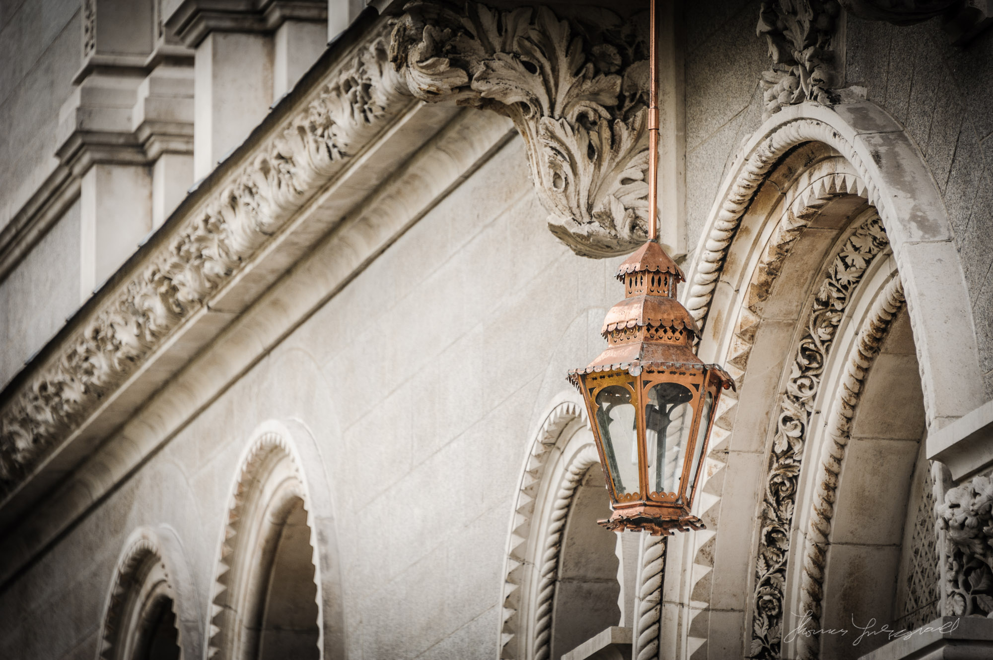 An ornate lamp hanging outside a doorway in Trinity College, Dublin.