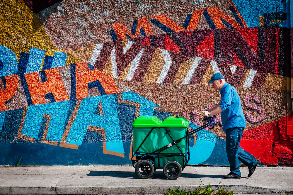 Postman walking against a grafitti covered wall