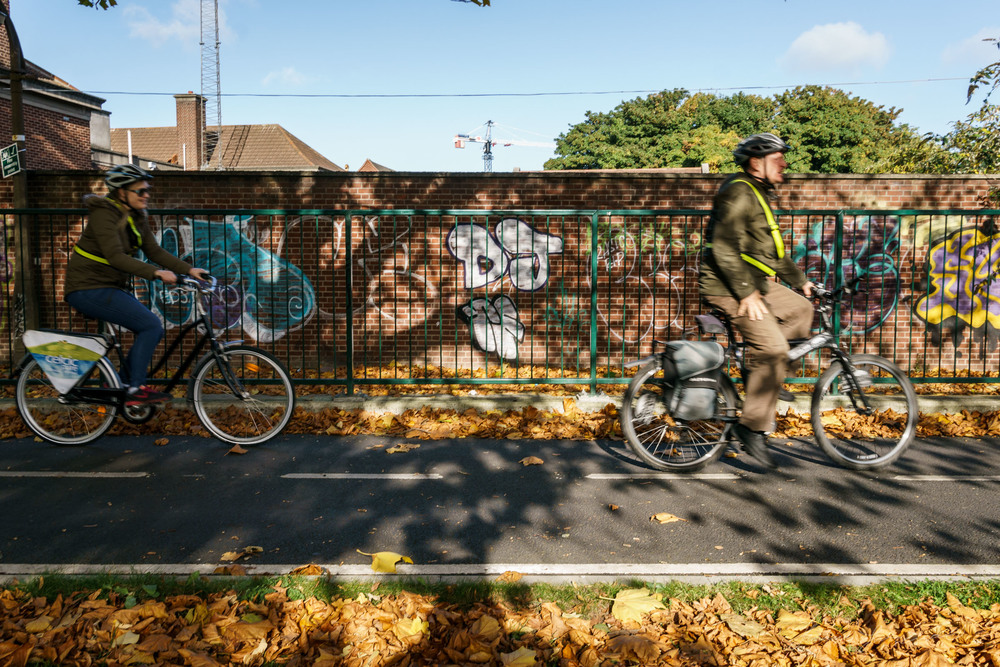 People cycling by a grafitti covered wall