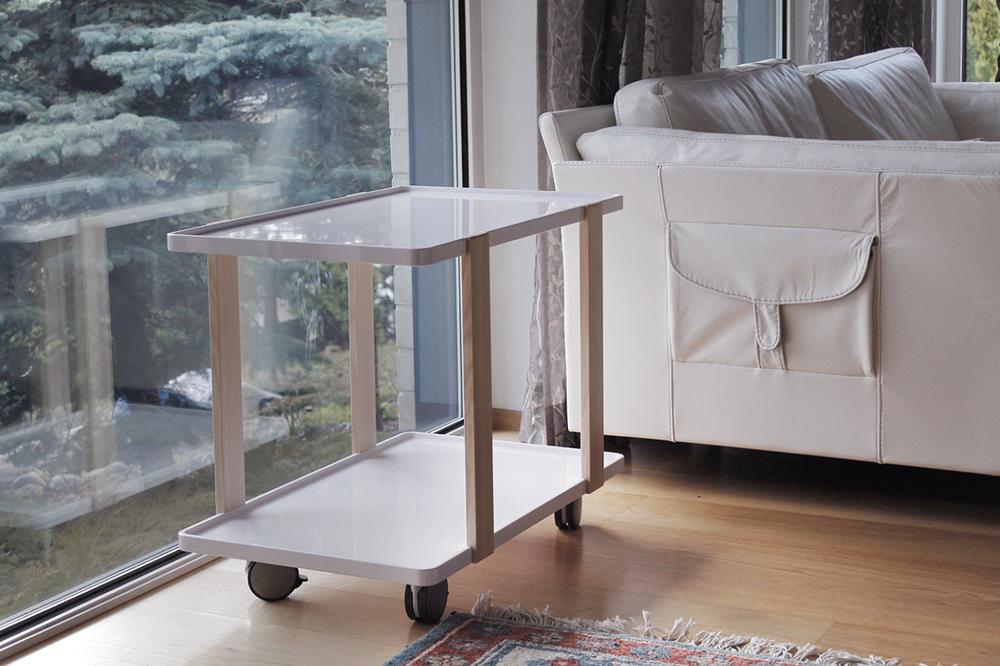 Pirteä kiiltomaalattu puinen tarjoiluvaunu toimii olohuoneen siirreltävänä sivupöytänä.