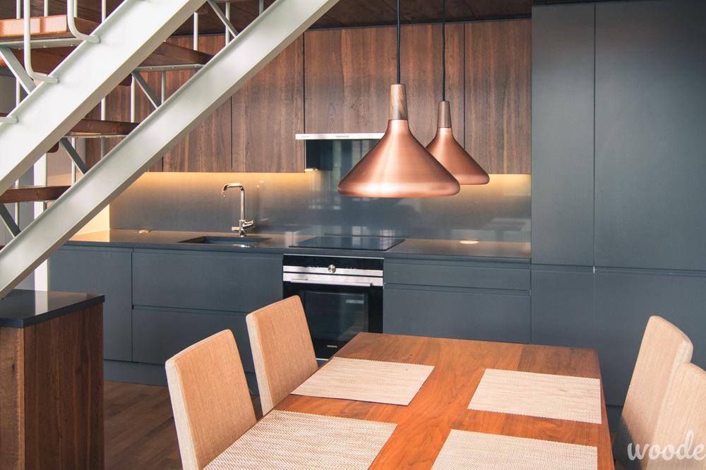 Loft-asunnon keittiö tuo vahvoilla sävyillä ryhtiä alakerran suureen tilaan.