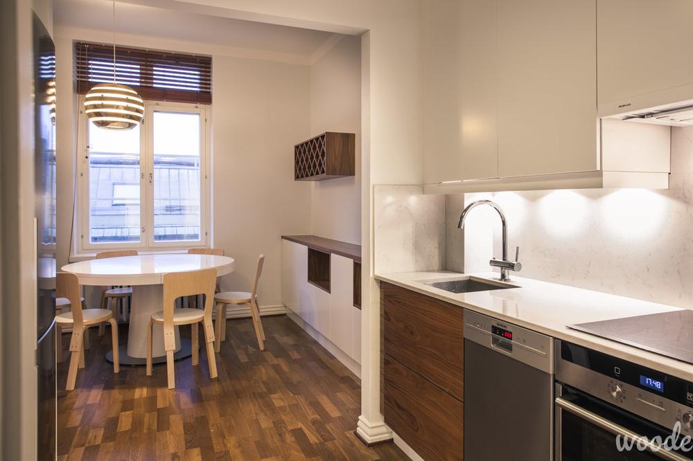 Pienen keittiön kalusteissa yhdisteltiin pähkinäpuuta ja vaaleaa kiveä.