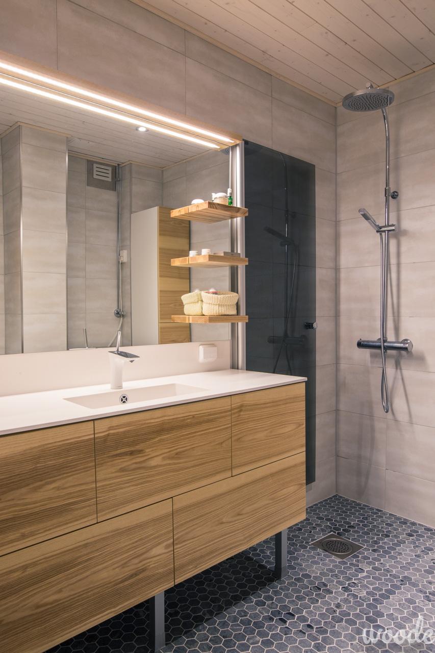 Kylpyhuoneessa yhdistyy kauniisti eläväiset puukalusteet ja luonnonkivilattia.