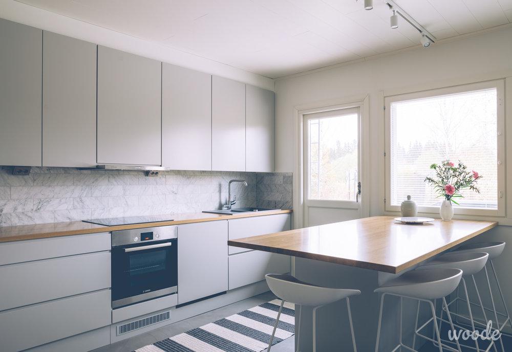 Tammiset työtasot luovat tyylikkään betoninharmaaseen keittiöön kodikasta lämpöä.