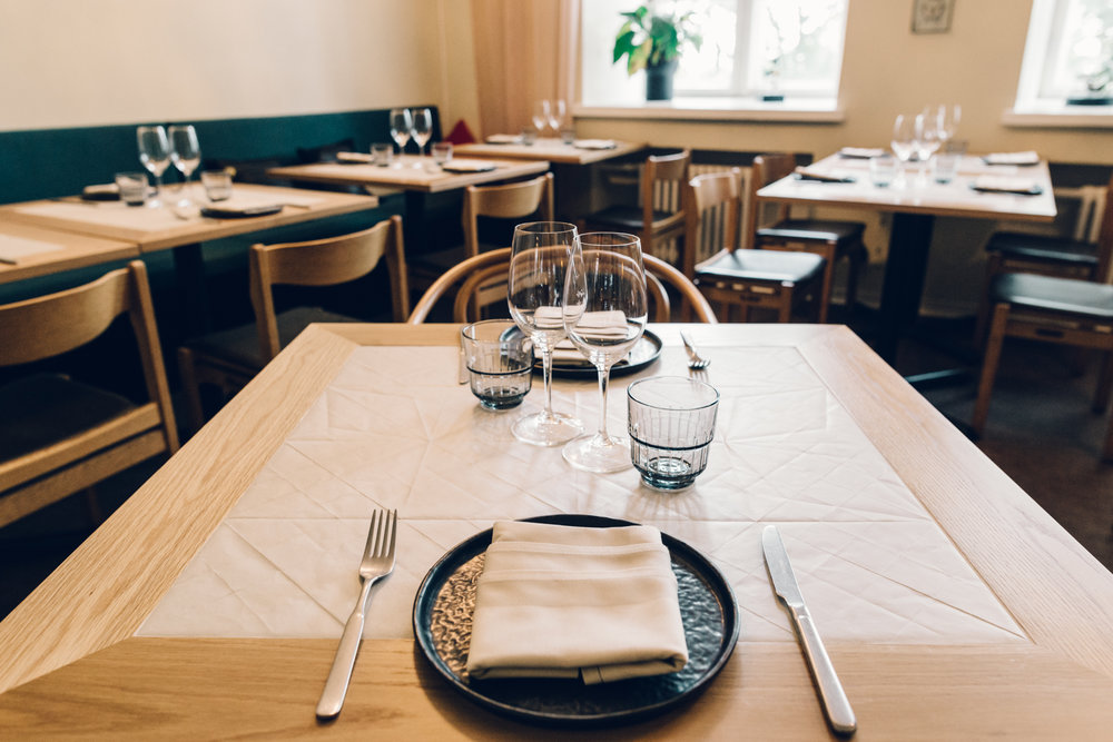Keraaminen laatta ruokapöydän keskellä kestää kuumat tarjoiltavat ja kovan kulutuksen. Tilasuunnittelu: A-J Silvennoinen & Tom Gustafsson.